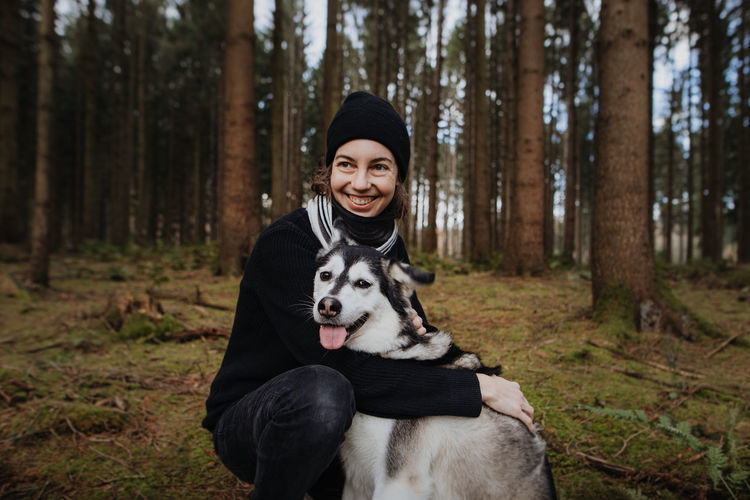 Portrait of smiling woman with dog in forest