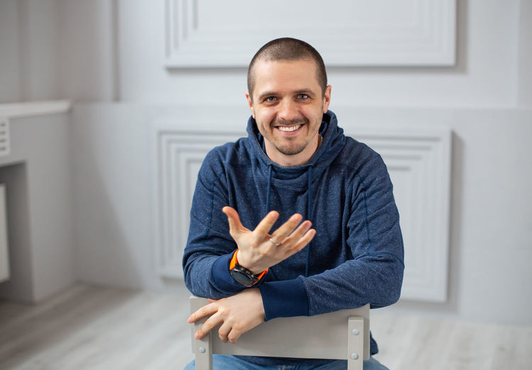 Smiling man in hoodie telling somethins to camera whilte sitting on chair in room Looking At Camera Portrait Smiling One Person Front View Happiness Indoors  Standing Waist Up Gesturing Men Emotion Young Adult Confidence  Casual Clothing Showing Adult Real People Cheerful