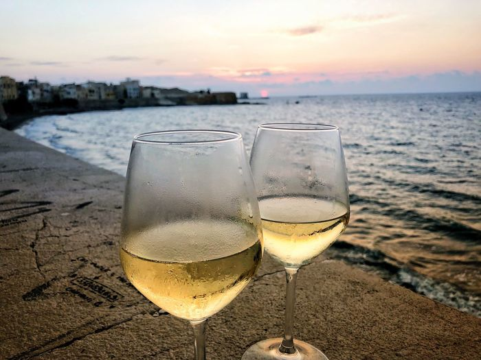 Close-up of wineglasses on retaining wall by sea against sky during sunset
