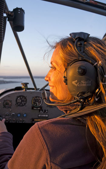 Smiling woman wearing headset while sitting in helicopter