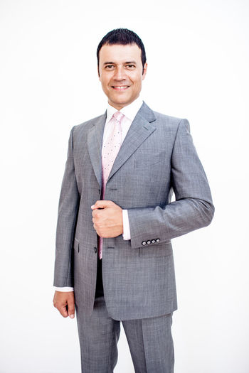 Man in classic suit on the white background. Studio shot. Classic Business Business Person Businessman Clothing Formalwear Front View Full Suit Indoors  Looking At Camera Males  Manager Men Menswear One Person Portrait Smile Smiling Standing Studio Shot Suit Three Quarter Length Well-dressed White Background White Backround