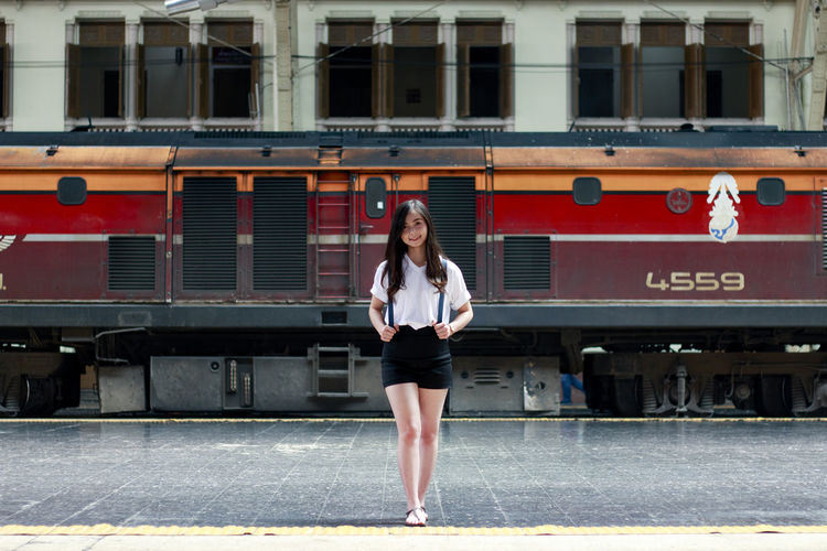 Portrait Of Young Woman Standing At Railroad Station Platform