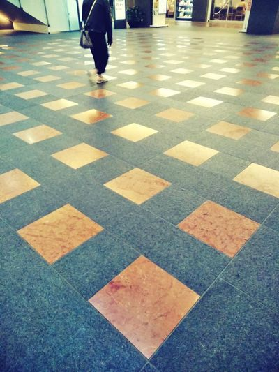 Low section of person walking on tiled floor