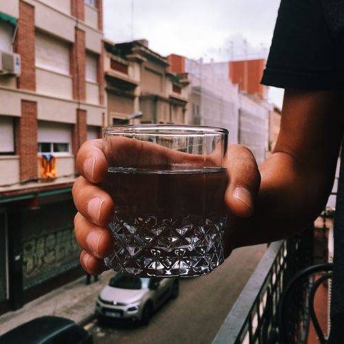 Young man with a glass of water in his hand in the balcony Outdoors Thirst Thirsty  Glass Of Water Water Human Hand Hand Human Body Part Holding Real People One Person Food And Drink Lifestyles Drink Refreshment Glass Glass - Material Close-up City