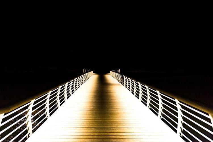 Footbridge against clear sky at night