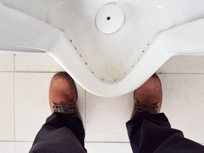 Low section of man standing by toilet bowl in public restroom