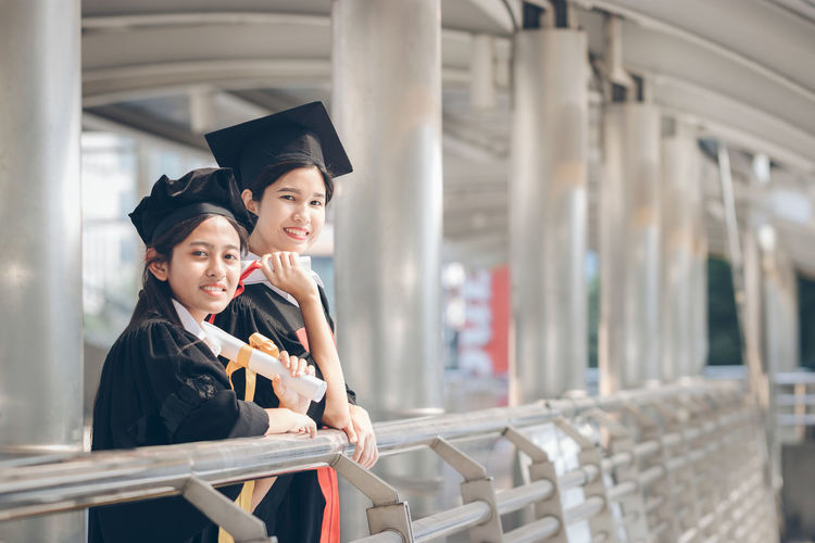 Two People Young Women Young Adult Togetherness Women Education Emotion Graduation Gown Student University Standing Adult Achievement Learning Looking Away Graduation Real People Positive Emotion Smiling Waiting Happiness Successful Degree Cityscape Certificate