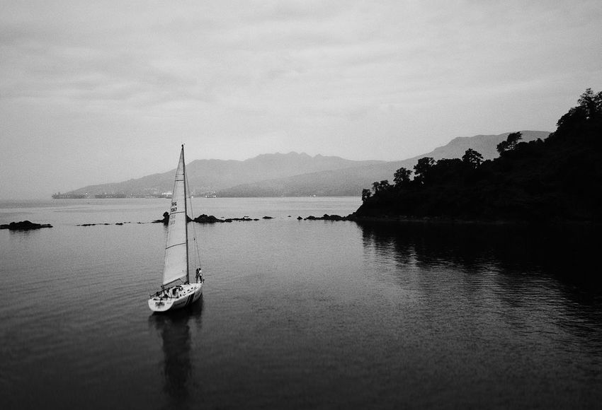 Sail away Moody Sky Wallpaper Art Island Black And White Black And White Photography Bnw Spark Dji Drone  Aerial Travel Travelphotography Sail Water Mountain Nautical Vessel Transportation Scenics Sky Nature Outdoors Mode Of Transport Tranquility Mountain Range Lake Day Tranquil Scene Moored Beauty In Nature EyeEmNewHere