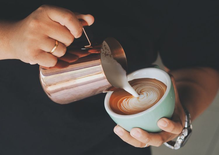 Barista pouring milk in coffee cup for making latte art. Black Background Close-up Day Drink Food And Drink Freshness Holding Human Body Part Human Hand Indoors  One Person People Real People Working