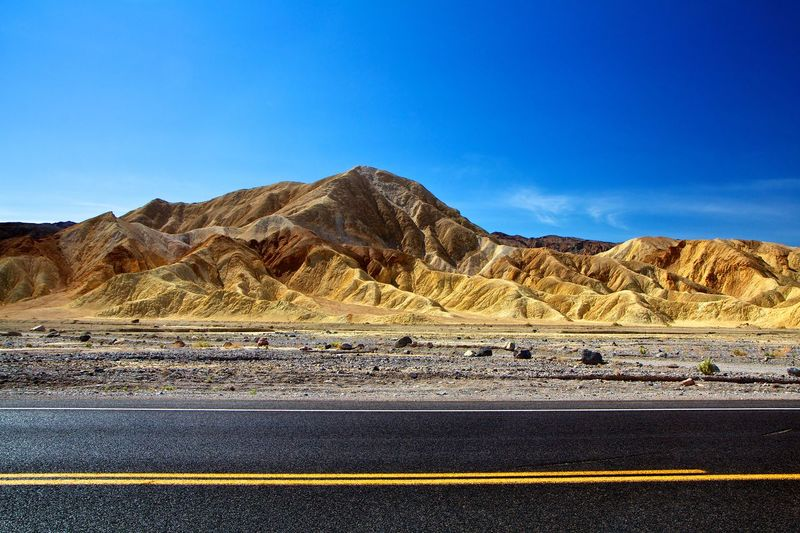 Desert lines California Death Valley Golden Hills Road Arid Climate Beauty In Nature Blue Clear Sky Day Desert Landscape Mountain Mountain Range Nature No People Outdoors Physical Geography Road Scenics Sky Street The Way Forward Transportation