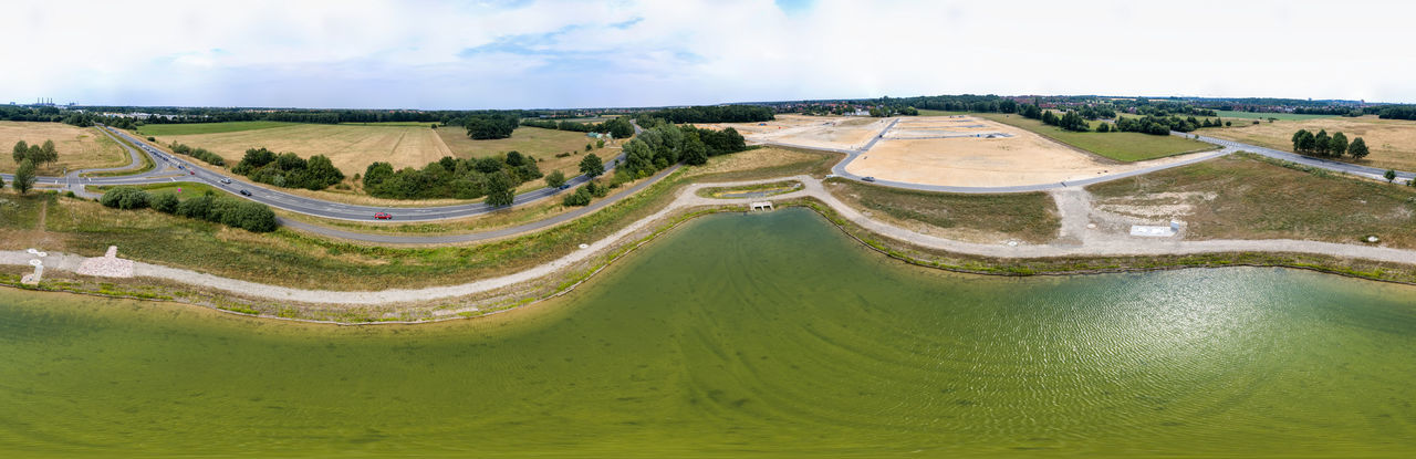 Panorama in high resolution, composed of photos with the drone, from the centre of a new rainwater retention basin to a new development and a country road Architecture Cloud - Sky Day Environment Golf Golf Course Grass Green - Golf Course Green Color Lake Landscape Nature No People Outdoors Panoramic Plant Scenics - Nature Sky Sport Water