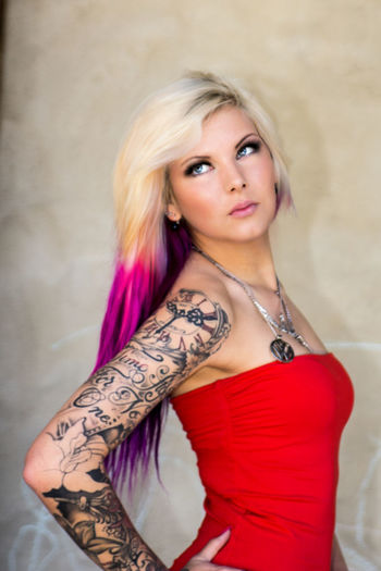 Beautiful Young Woman With Tattoo And Dyed Hair Standing Against Wall