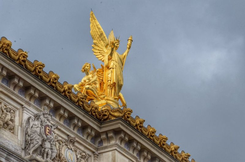 Low angle view of angel statue on building against cloudy sky