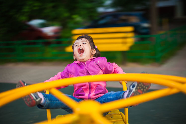 Happy girl playing on slide at playground