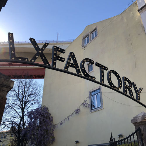 Entrance to LX Factory in Lisbon, Portugal Lisbon Portugal Architecture Built Structure Building Exterior Low Angle View Clear Sky Sky Building Nature Blue Day No People Outdoors City Tree Communication Residential District Wall - Building Feature Text Graffiti Sunlight Lx Factory