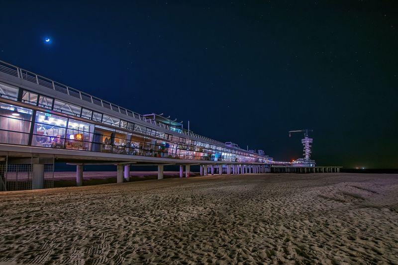Pier at sandy beach against sky during night at scheveningen