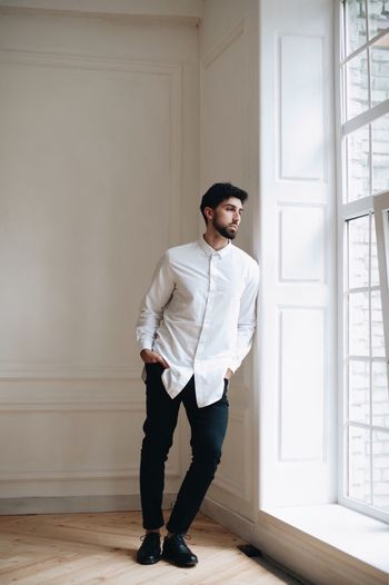 a young man of oriental appearance sits by the window One Person Full Length Standing Young Adult Young Men Lifestyles Men Real People Wall - Building Feature Front View Window Casual Clothing Indoors  Adult Day Hands In Pockets Contemplation Males  Looking Button Down Shirt