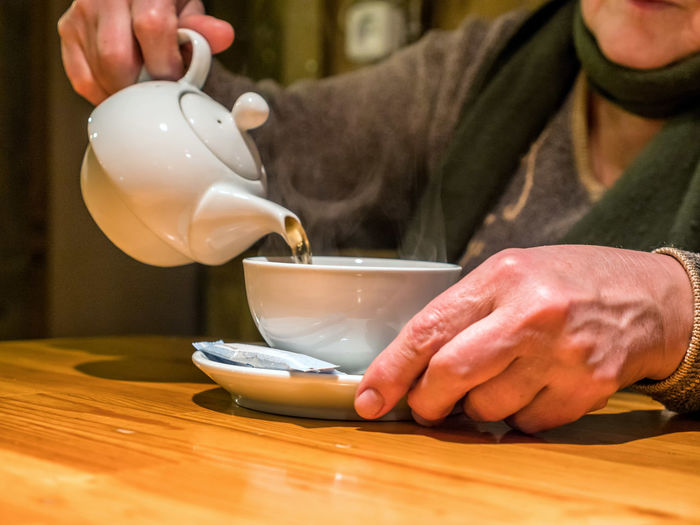 Closeup view tea pot pouring drink into cup in senior hands Pouring Tea Close-up Day Drink Filling Focus On Foreground Food And Drink Freshness Holding Human Hand Indoors  Men Midsection Occupation One Person People Piggy Bank Pot Preparation  Real People Table