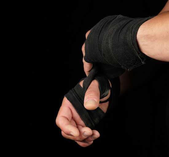 Cropped hands with straps against black background