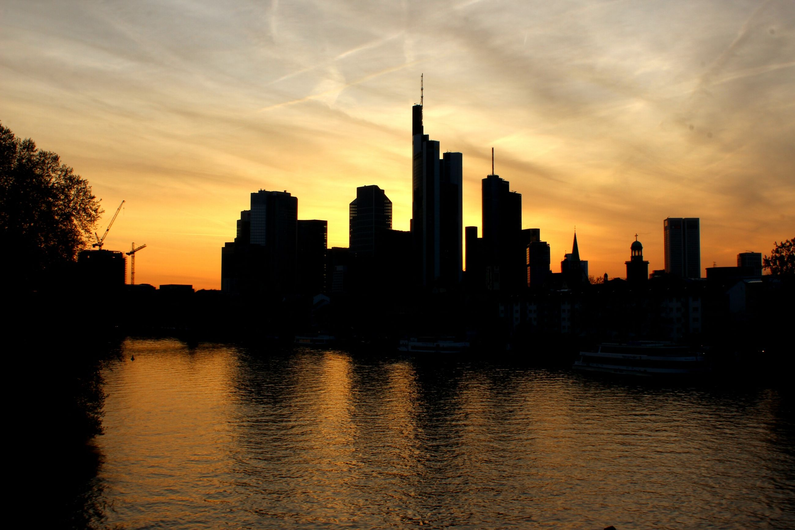 sunset, building exterior, architecture, built structure, water, silhouette, waterfront, city, sky, skyscraper, reflection, urban skyline, river, cityscape, cloud - sky, skyline, orange color, tower, tall - high, modern