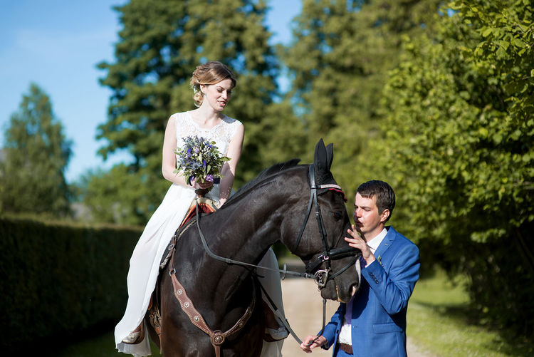 Young Bride Riding Horse On Field