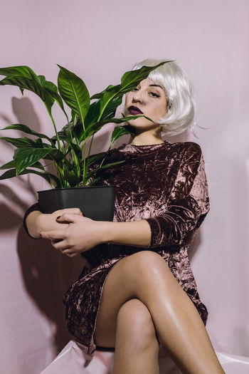 Young woman sitting with pot plant