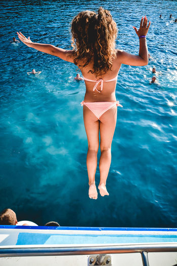 Rear view of woman jumping in swimming pool