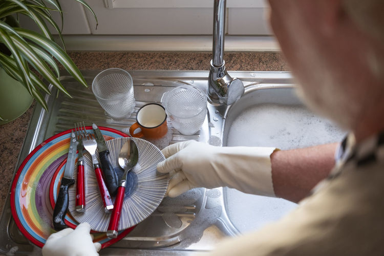 Midsection of senior man cleaning dish at kitchen