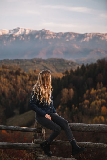 Beautiful blonde woman relaxing on the fence in the autumn mountains at sunset. travel concept.