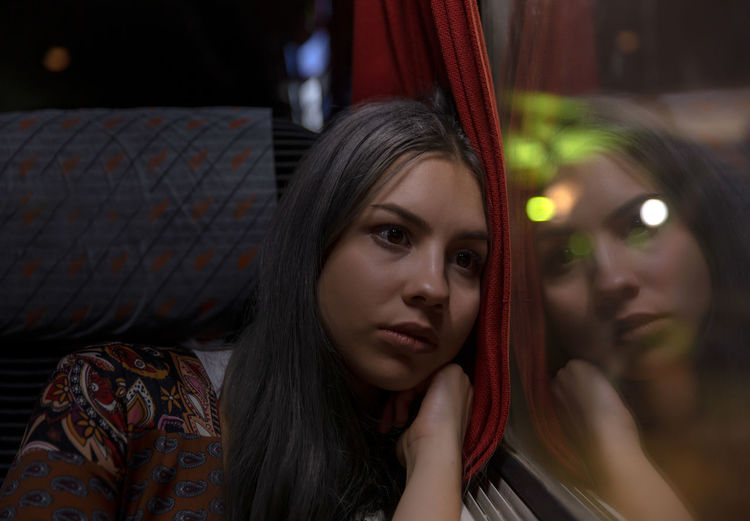 Beautiful young woman looking away while leaning on train window