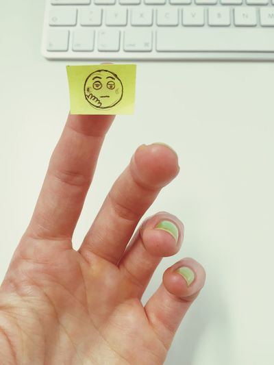 Close-up of cropped hand showing sad face on adhesive note