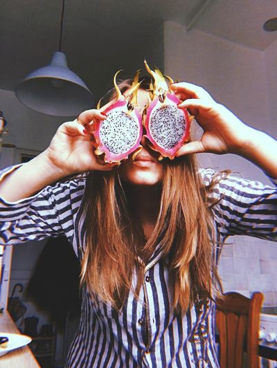Young woman holding dragonfruit at home