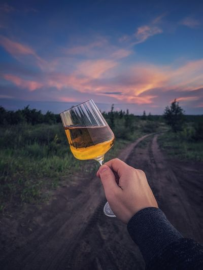Midsection of person holding drink against sky during sunset