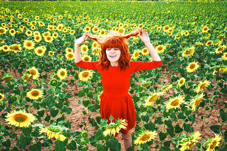 Smiling young woman with yellow flowers in field