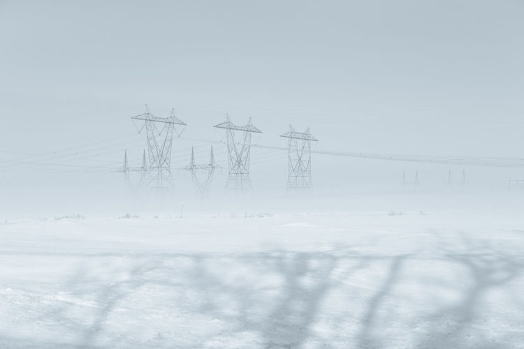 Electricity pylon on field against sky during winter