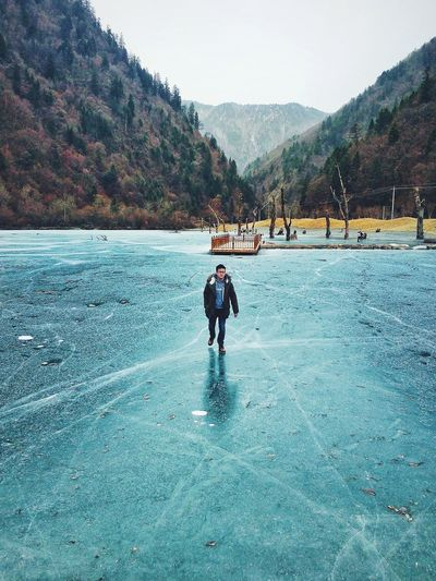 Full Length Of Young Man Walking On Frozen Lake