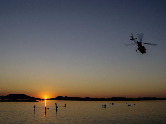 Silhouette helicopter flying over people in sea against clear sky during sunset