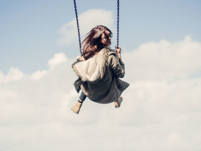 Low angle view of woman on swing against cloudy sky