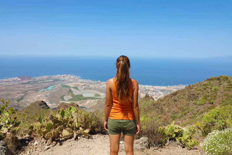Rear view of woman looking at sea while standing on mountain against sky