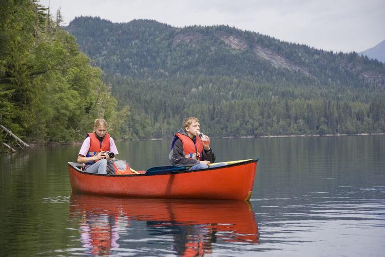 Siblings Wearing Life Jacket Canoeing On Lake Against Mountain
