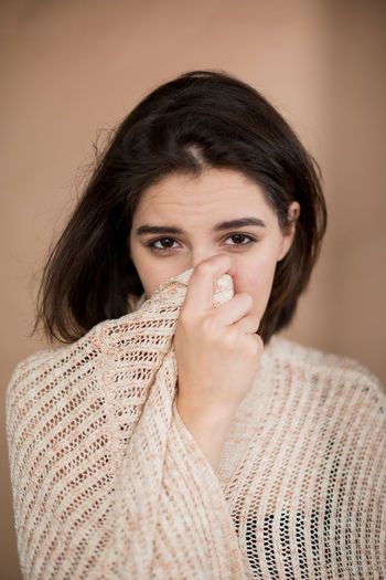 Portrait of young woman covering face against wall
