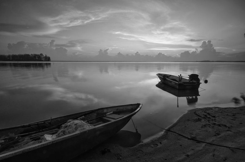 Fine art Black & white image of beautiful landscape of the beach at morning. Fisherman boat and clouds reflecting in the water. Long exposure. Black And White Seascape Beach Landscape Fine Art Amazing View Amazing Black&white Fine Art Photography Black Wallpaper EyeEm Nature Lover EyeEm Blackandwhite Art Backgrounds Kelantan Malaysia Sunset Sunrise Water Nautical Vessel Lake Moored Reflection Rowboat Sky Fishing Boat Fishing Industry Fisherman Fish Market