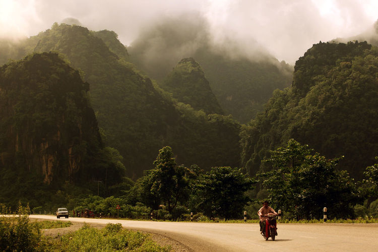 People traveling on motorcycle against mountains