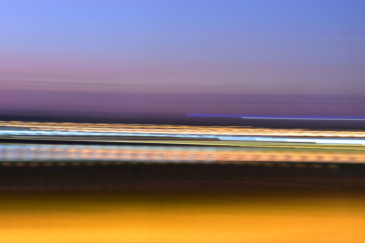 Blurred motion of light trails in sea against sky at sunset