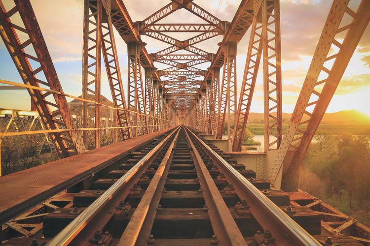 Empty railway bridge against sky during sunset