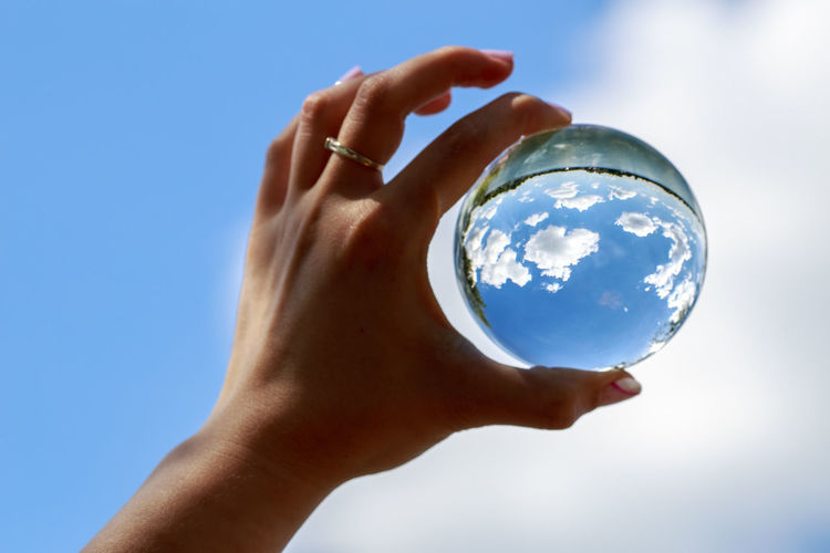 Cropped image of woman holding crystal ball against blue sky