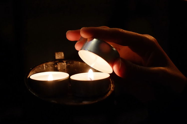 Black Background Burning Candle Close-up Diya - Oil Lamp Flame Glowing Heat - Temperature Holding Human Body Part Human Hand Illuminated Indoors  Night Oil Lamp One Person People Real People Spirituality Tea Light