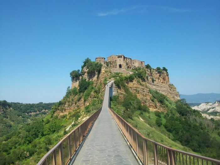 Low angle view of walkway leading towards castle against blue sky