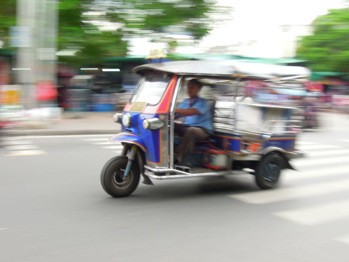 Blurred motion of man riding motor scooter on road
