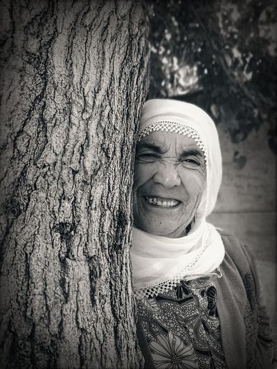 Portrait of a smiling young woman against tree trunk